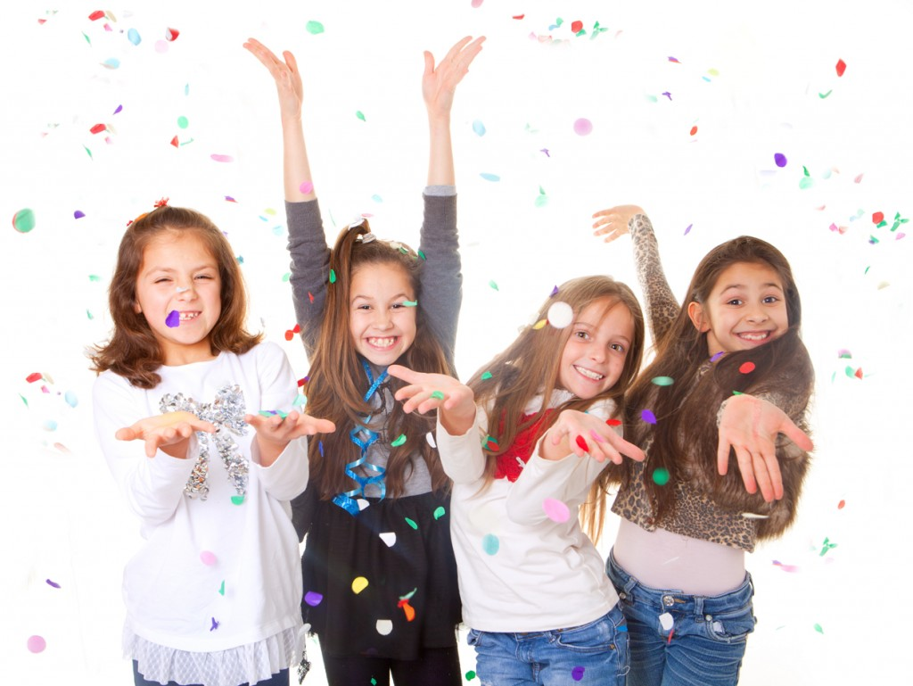 Happy young girls at a party with confetti.
